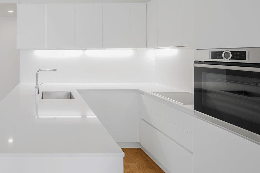 Ljust kök med vita köksluckor och vit bänkskiva