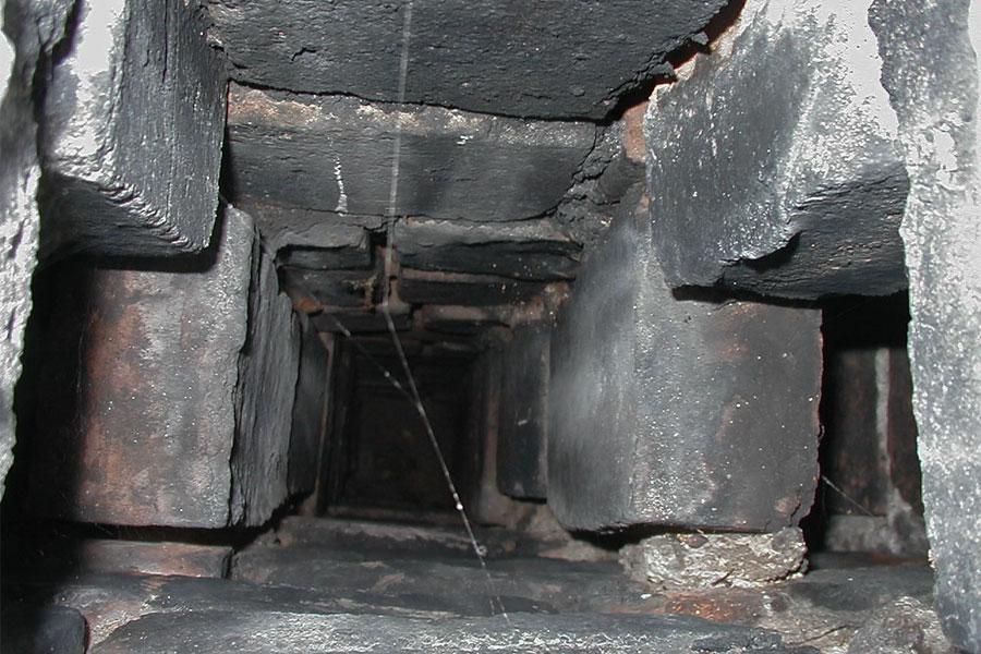 Bilden visar stenar som saknas på skiljeväggen i skorstenen.