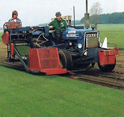 Med stora moderna maskiner skördas den färdiga gräsmattan. Två man betjänar maskinen.