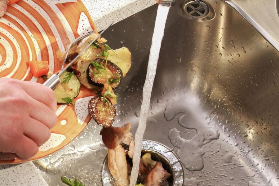 Matrester skjuts ner i en avfallskvarn