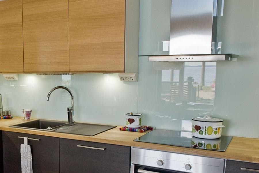Stänkskydd av glas i kök med träluckor