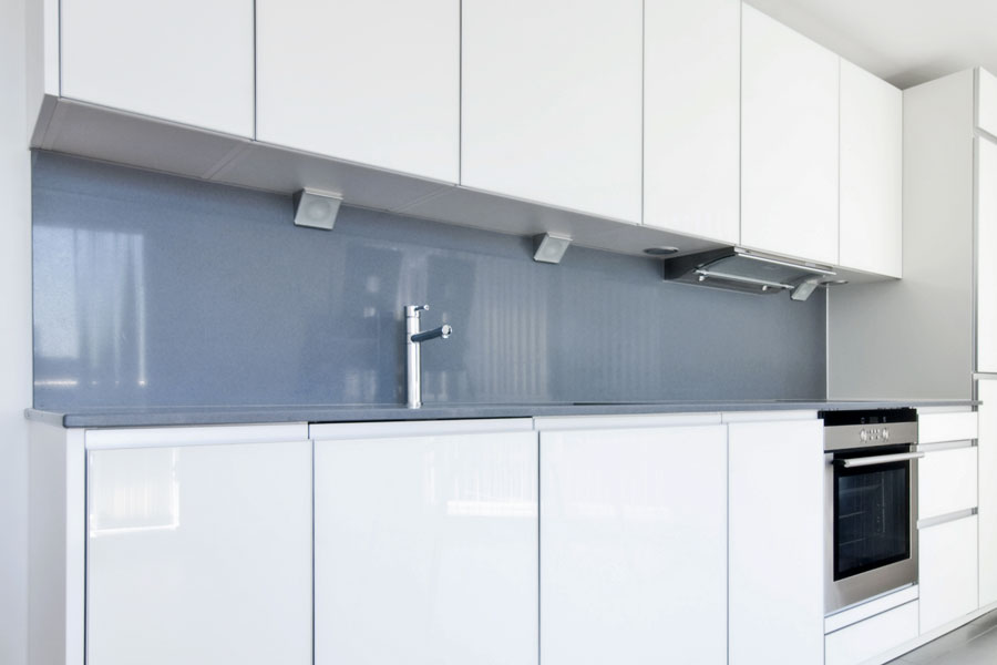 Stänkskydd av glasemalj och komposit i modernt vitt kök