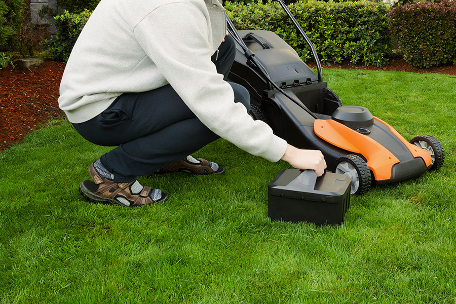 Byter batteri på batteridriven gräsklippare