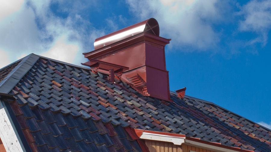 Röd skorstenshuv med plåtintäckt skorsten