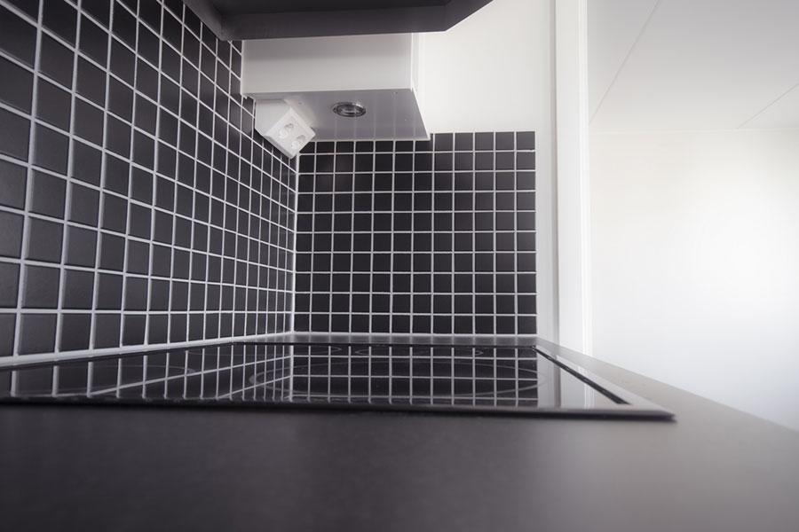 Mosaik ovanför bänkskiva och spis i kök