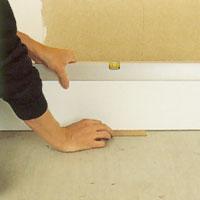 Provställ en sockelbräda på golvet eller på de utlagda passbitarna