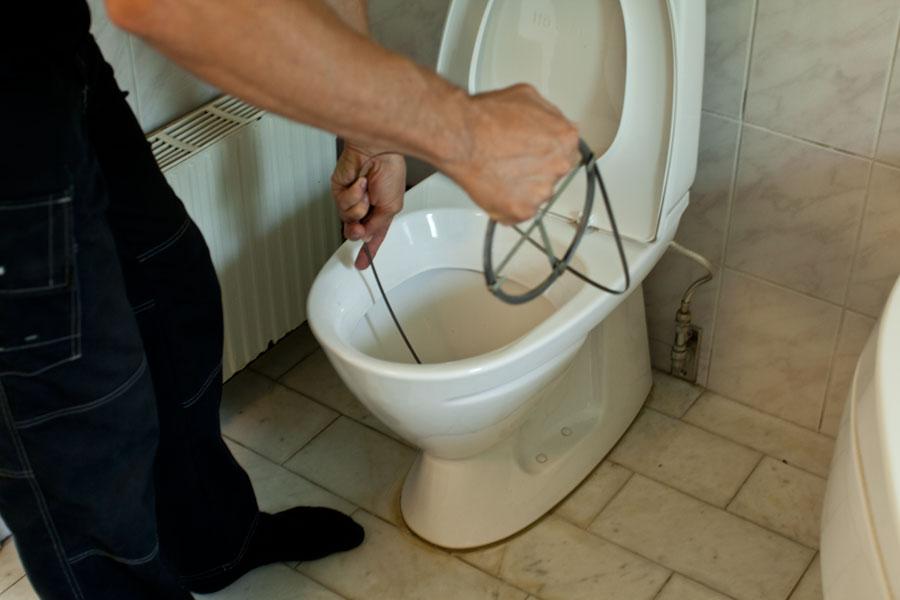 Drar rensband genom avloppet i toaletten för att få bort stopp