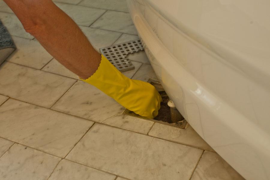Rensar bort smuts i golvbrunn med diskhandskar