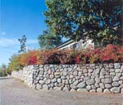För stabilitetens skull bör du välja mindre stenar högre upp på muren