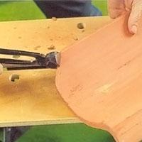 Hovtång som klipper i tegelpanna