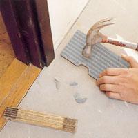 Knacka bort några flisor på klinkerplattans undersida.