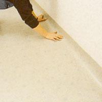 Om väggen buktar lägg plastmattan några cm upp på väggen.