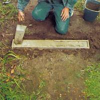 Sätt en brädbit i varje kortände som stopp för betongen