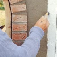 Jämna till alla kanter intill husväggen och tegelstensraden med en liten torr pensel.