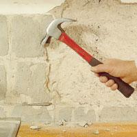 Knacka med en hammare mot väggen så att lös puts släpper