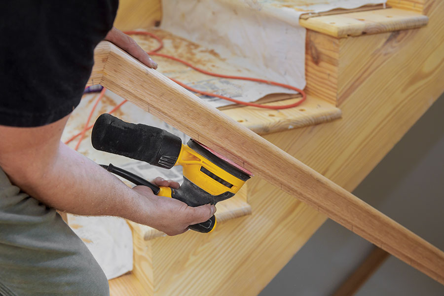 Renoverar trätrappa med slipmaskin