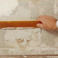 Stryk bort överflödigt bruk så att väggen blir plan