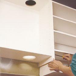 Köksskåpet för köksfläkten sätts på plats