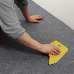 Slätar ut heltäckningsmattan med en spackel för att få bort veck och bubblor