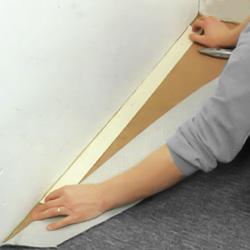 Lägger tejpremsor tätt intill väggen
