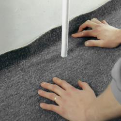 Pressar heltäckningsmattan mot golvsockeln