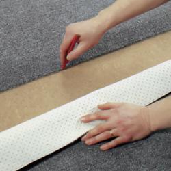 Viker upp mattan och markerar med blyertspenna på golvytan