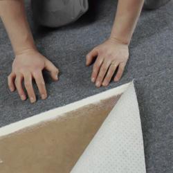 Pressar fast kanten på heltäckningsmattan mot tejpen