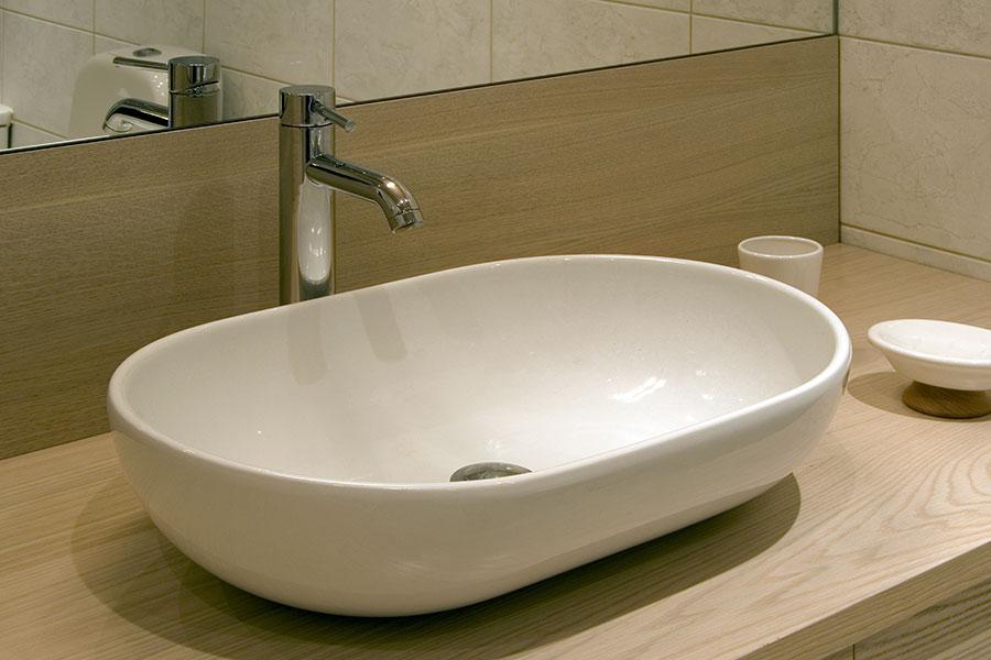 Ovanpåliggande ovalt tvättställ på bänkskiva av trä