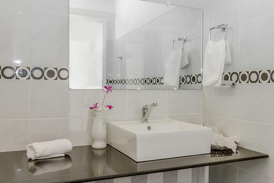 Ovanpåliggande tvättställ ovanpå bänkskiva i badrum