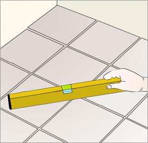kontrollerar klinkergolv med vattenpass